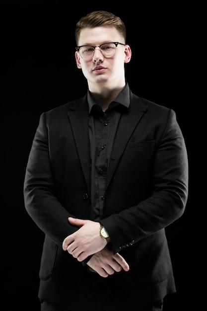 Retrato de confianza guapo elegante empresario responsable en vasos con mano en pie Foto Premium