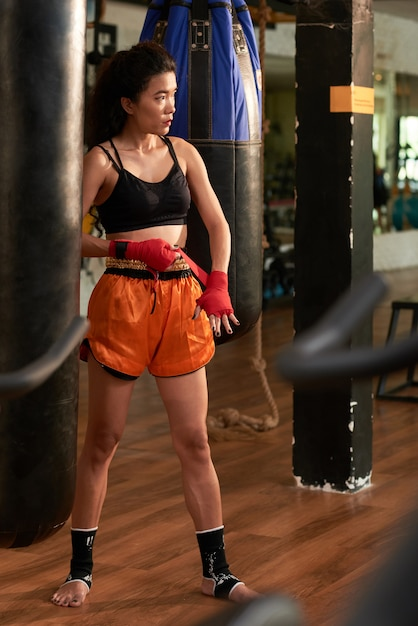 Retrato de cuerpo entero de boxeador de muay thai envolviendo la banda roja en la muñeca antes del entrenamiento Foto gratis