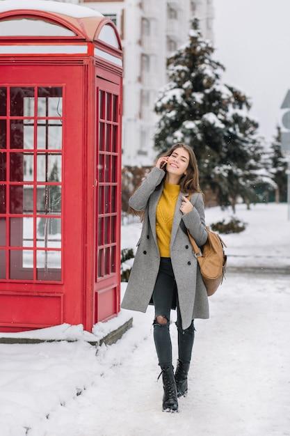 Retrato de cuerpo entero de una elegante mujer joven con abrigo gris y pantalones rotos hablando por teléfono, caminando por la calle nevada. foto de mujer impresionante de pie cerca de la caja de llamada roja y sosteniendo el teléfono inteligente. Foto gratis