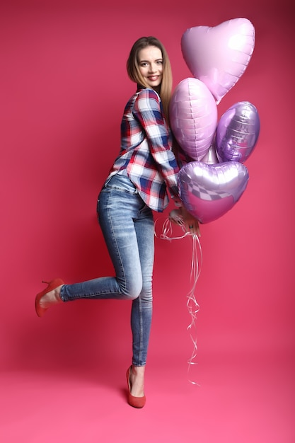 Retrato de cuerpo entero de feliz bella mujer joven con globos de colores Foto Premium