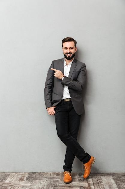 Retrato de cuerpo entero de hombre atractivo posando en la cámara con una amplia sonrisa apuntando el dedo índice a un lado, aislado en gris Foto gratis