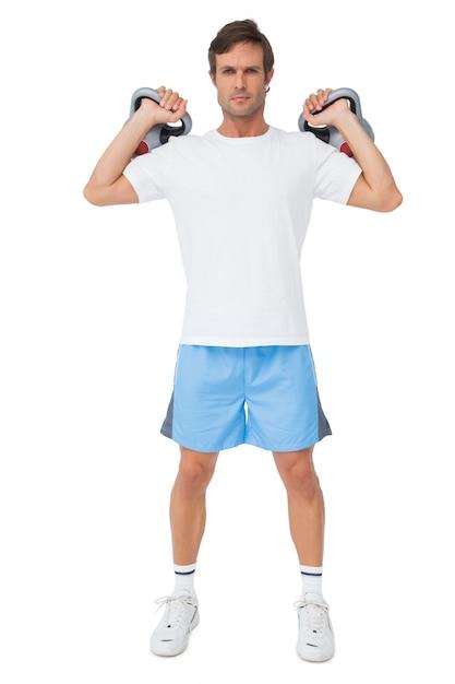 69f3e2e23495 Retrato de cuerpo entero de un hombre en forma elevación kettlebells |  Descargar Fotos premium