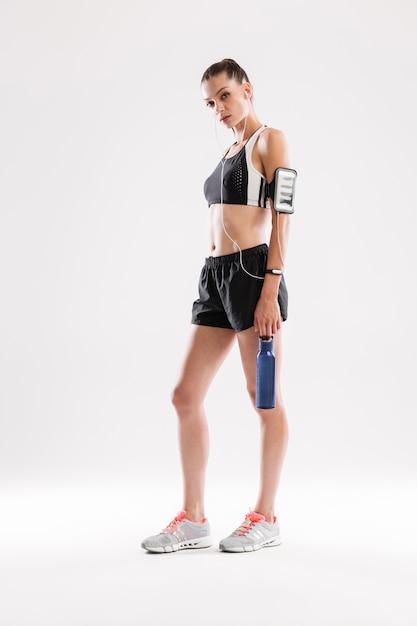 Retrato de cuerpo entero de una joven deportista agotada en auriculares Foto gratis