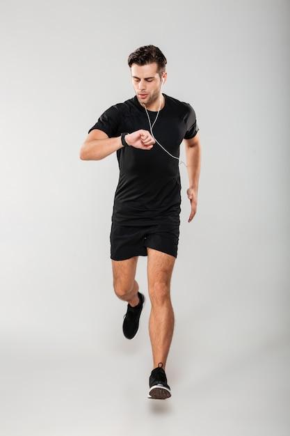 Retrato de cuerpo entero de un joven deportista en forma de auriculares Foto gratis