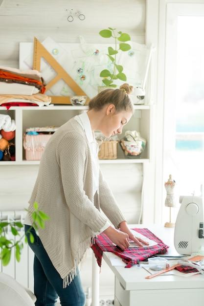 Retrato de una mujer atractiva que trabaja con un patrón de costura ...