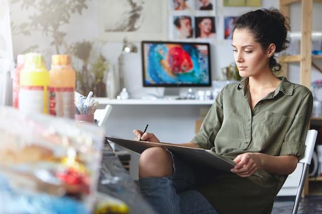 Retrato del diseñador confiado joven moreno confiado de la mujer en vaqueros rasgados que trabaja en nuevo proyecto del arte, haciendo dibujos o bosquejos en la tableta. hermosa artista femenina absorta con su trabajo creativo Foto gratis