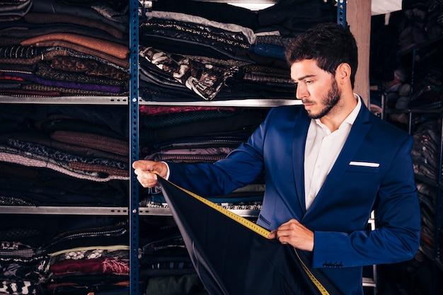 Retrato de un diseñador de moda tomando medidas de tela en su tienda Foto gratis