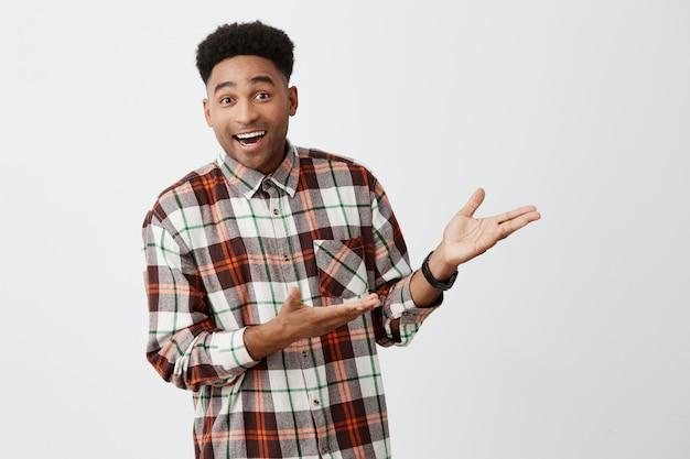 Retrato de divertido joven hermoso de piel oscura con peinado afro en camisa casual sonriendo, mostrando la pared blanca con las manos con expresión emocionada y feliz Foto gratis