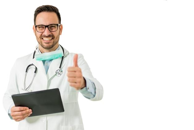 Retrato del doctor de sexo masculino joven con el pulgar que sostiene la tableta digital aislada en el blanco Foto Premium