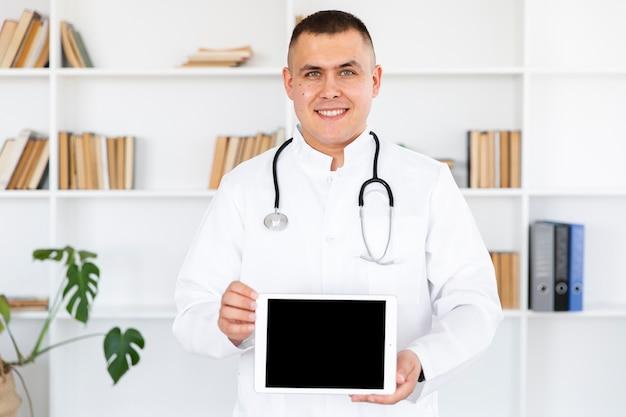 Retrato del doctor sonriente sosteniendo foto maqueta Foto gratis