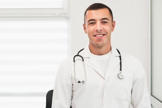 Retrato del doctor sonriente vistiendo túnica blanca Foto gratis