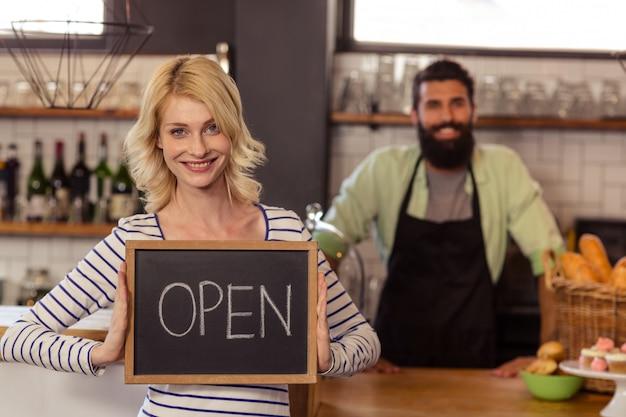 Retrato de dos camareros casuales sosteniendo un tablero escrito abierto Foto Premium