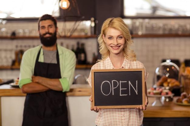 Retrato de dos camareros sosteniendo un tablero escrito abierto Foto Premium