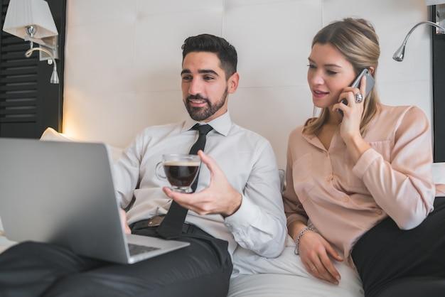 Retrato de dos jóvenes empresarios trabajando juntos en la computadora portátil en la habitación del hotel. concepto de viajes de negocios. Foto gratis