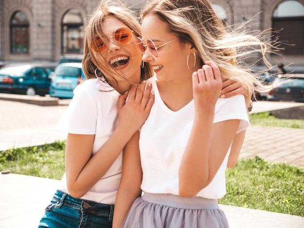 Retrato de dos jóvenes hermosas rubias sonrientes chicas hipster en ropa de moda verano camiseta blanca. . Foto gratis