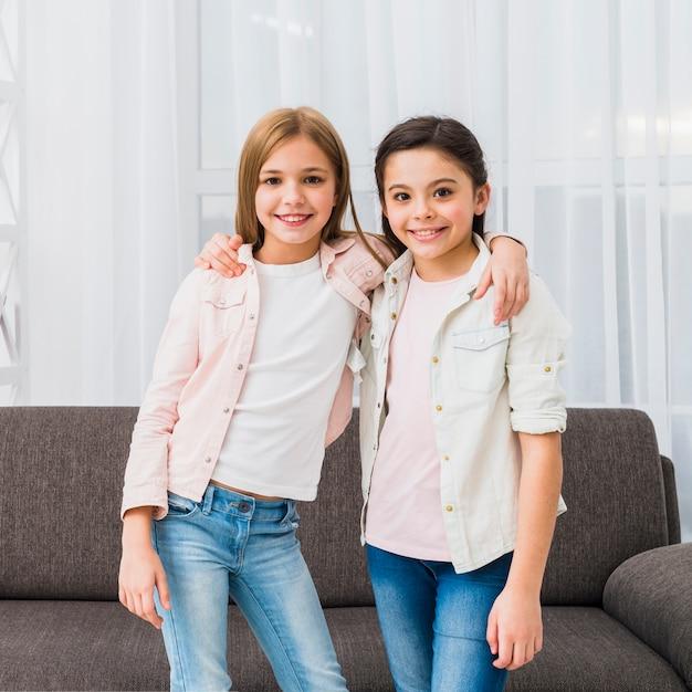 Retrato De Dos Muchachas Bonitas Sonrientes Con Sus Brazos