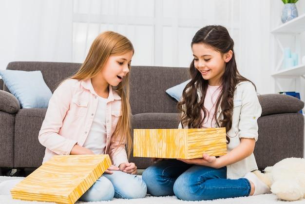 Retrato de dos muchachas sonrientes que miran la caja de regalo que se sienta en la sala de estar Foto gratis