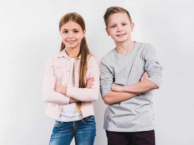 El retrato de dos el muchacho y la muchacha sonrientes con sus brazos cruzaron la mirada a la cámara contra el fondo blanco Foto gratis
