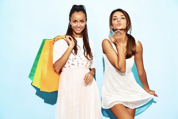 Retrato de dos mujeres morenas sonrientes con estilo jovenes que sostienen los panieres. mujeres vestidas con ropa hipster de verano. modelos positivos posando sobre pared azul y dando beso de aire Foto gratis
