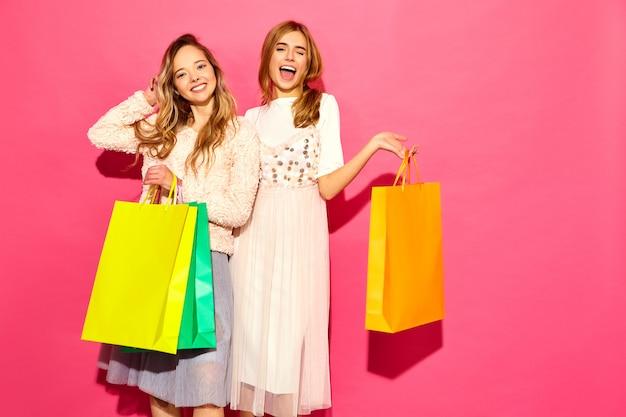 Retrato de dos mujeres rubias sonrientes elegantes jovenes que sostienen los panieres. mujeres vestidas con ropa hipster de verano. modelos positivos posando sobre pared rosa Foto gratis