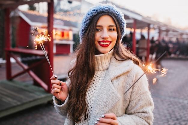 Retrato de elegante mujer de pelo castaño con elegante bata blanca con luces de bengala. foto al aire libre de la romántica chica europea en boina azul posando con luces de bengala en la ciudad de desenfoque Foto gratis