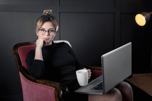 Retrato de empresaria adulta tomando un café en la oficina Foto gratis