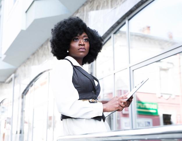 Retrato de la empresaria africana joven que sostiene el tablero que mira lejos Foto gratis