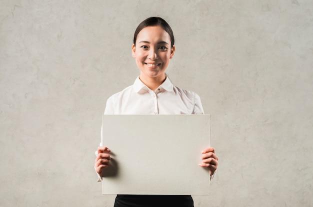 Retrato de una empresaria asiática joven sonriente que muestra el cartel en blanco Foto gratis