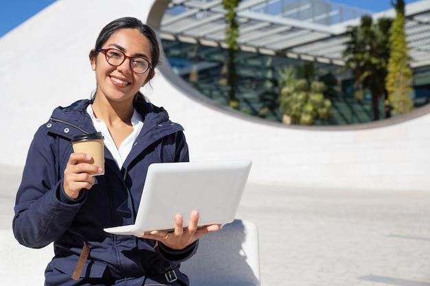 Retrato de la empresaria feliz que tiene descanso para tomar café al aire libre Foto gratis