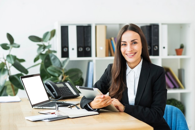 Retrato de una empresaria joven confiada en la oficina moderna Foto gratis