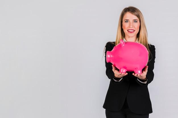 Retrato de una empresaria joven que sostiene el piggybank rosado grande disponible contra el fondo gris Foto gratis