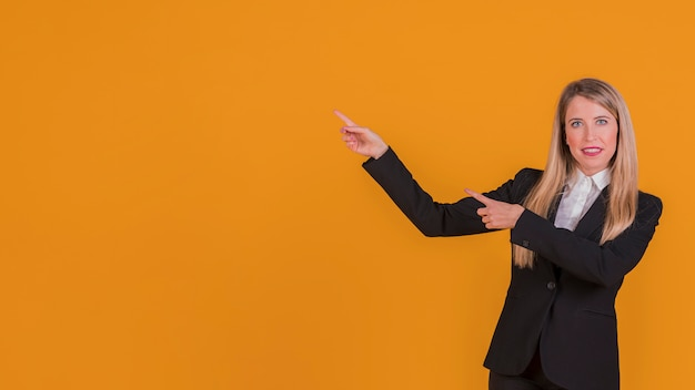 Retrato de una empresaria joven sonriente que presenta algo contra un fondo naranja Foto gratis
