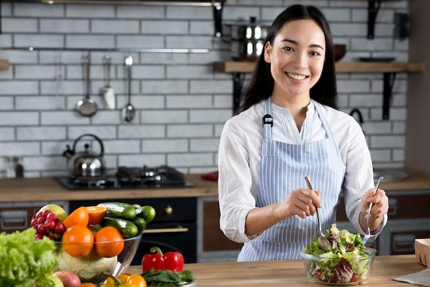 Retrato de la ensalada de mezcla de la mujer asiática en cocina Foto gratis