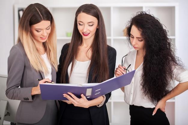 Retrato de equipo de mujeres empresarias felices de pie en el pasillo de la oficina, mirando a cámara, sonriendo. Foto Premium