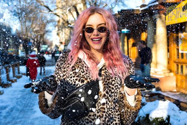 Retrato de estilo de vida alegre al aire libre de una mujer bonita con pelos rosados inusuales, con chaqueta de piel de leopardo de cuerpo moderno, gafas de sol estilo vintage de los 90 y riñonera, ropa de calle grunge, ciudad de la nieve marchita. Foto gratis