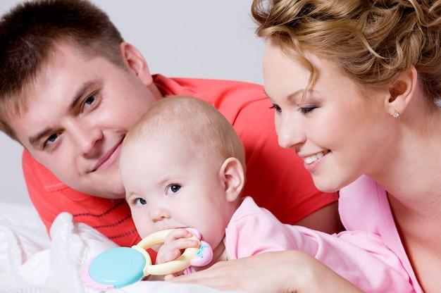 Retrato de estilo de vida de la hermosa joven familia feliz acostado en la cama en casa Foto gratis