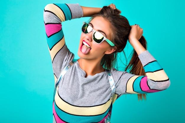 Retrato de estilo de vida de moda de mujer divertida alegre, labios carnosos sexy, gafas de sol espejadas, sosteniendo sus pelos como dos colas de caballo, colores primaverales, fondo de menta. emociones lindas, mujer de moda. Foto gratis
