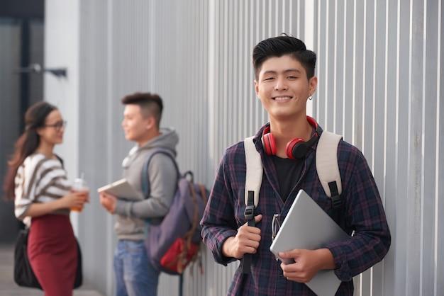 Retrato de estudiante asiático sonriente Foto gratis