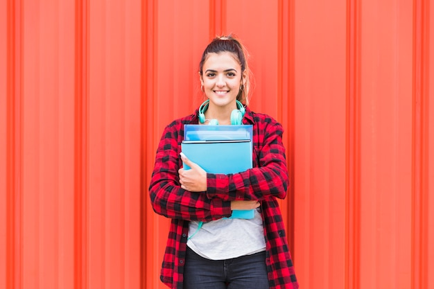 Retrato del estudiante bonito en los libros que se sostienen casuales elegantes en la mano que se opone a la pared que mira a la cámara Foto gratis