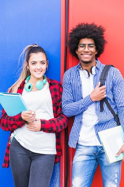 Retrato de estudiante femenino y masculino diverso sonriendo a la cámara contra la pared Foto gratis