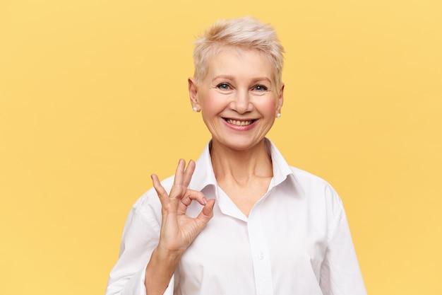 Retrato de exitosa empresaria de mediana edad confiada con el pelo corto teñido con una amplia sonrisa haciendo un gesto de ok, regocijándose por un buen trato rentable y un gran ingreso anual Foto gratis
