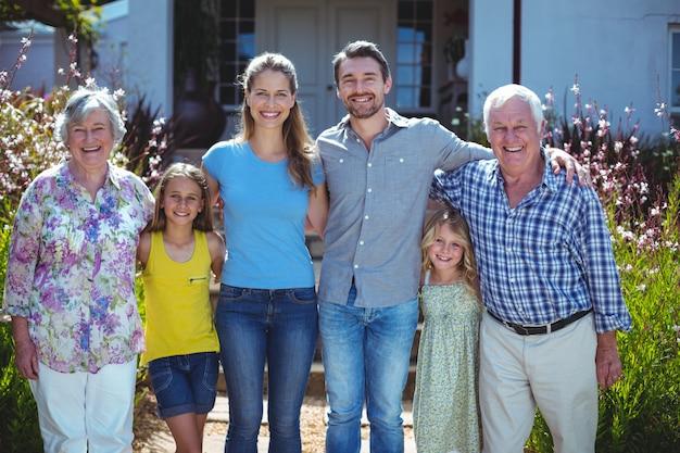 Retrato de familia feliz multigeneración contra casa Foto Premium
