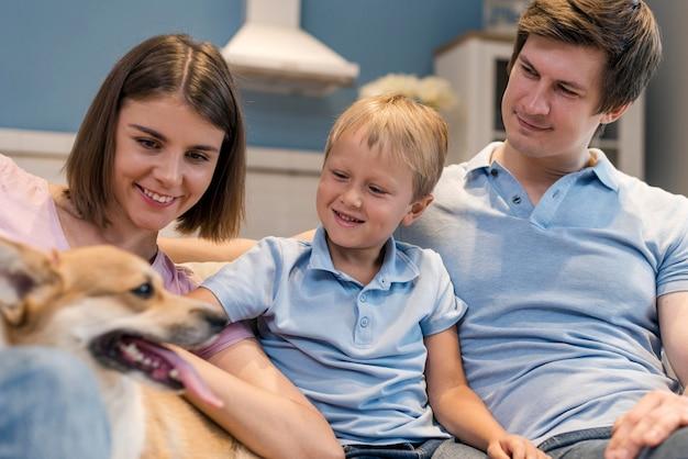 Retrato de familia jugando junto con perro Foto Premium