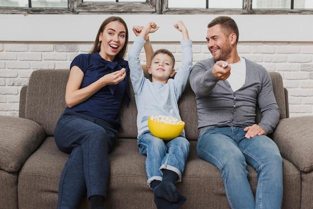 Retrato de familia viendo una película Foto gratis