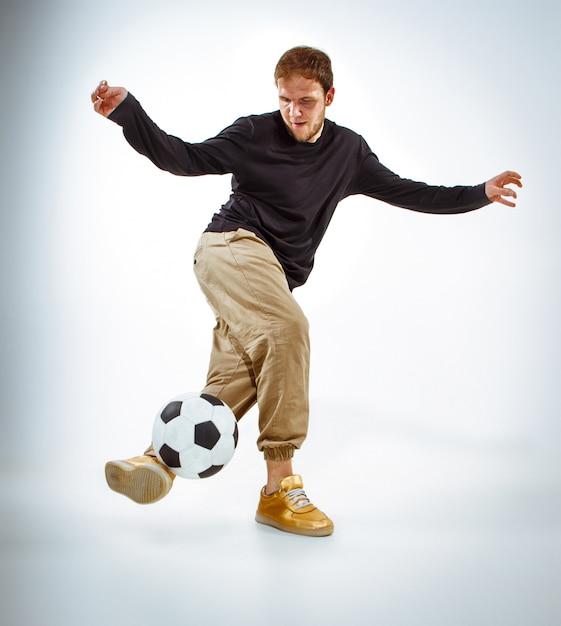 Un retrato de un fan con la bola en la pared gris del estudio. estilo libre. Foto gratis
