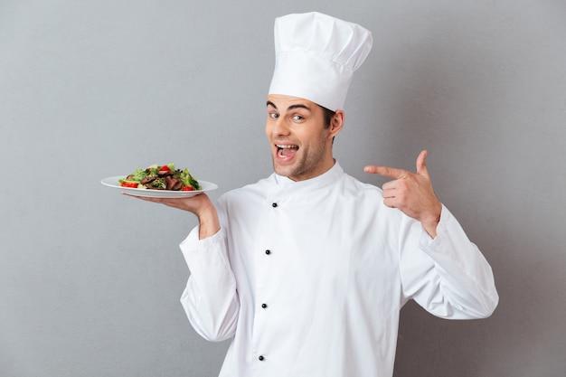 Retrato de un feliz chef hombre vestido con uniforme Foto gratis