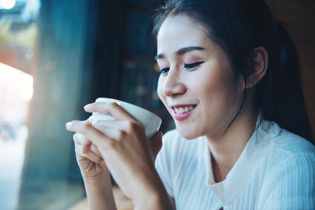 Retrato de feliz hermosa mujer con taza en las manos Foto gratis