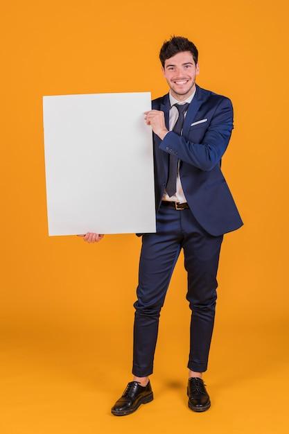 Retrato feliz de un hombre de negocios joven que muestra el cartel en blanco blanco que se sostiene a disposición Foto gratis