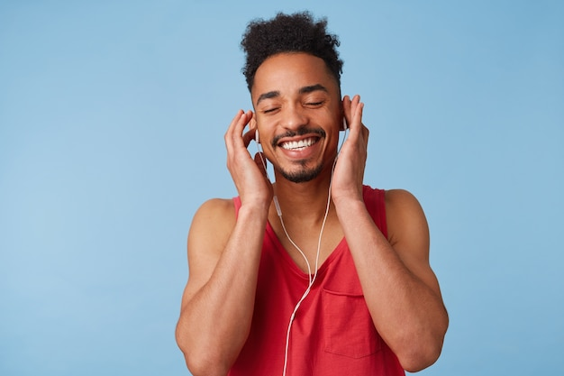 Retrato de feliz joven afroamericano se siente muy bien, use auriculares, cierre los ojos y disfrute de un nuevo álbum de su banda favorita, aislado. Foto gratis