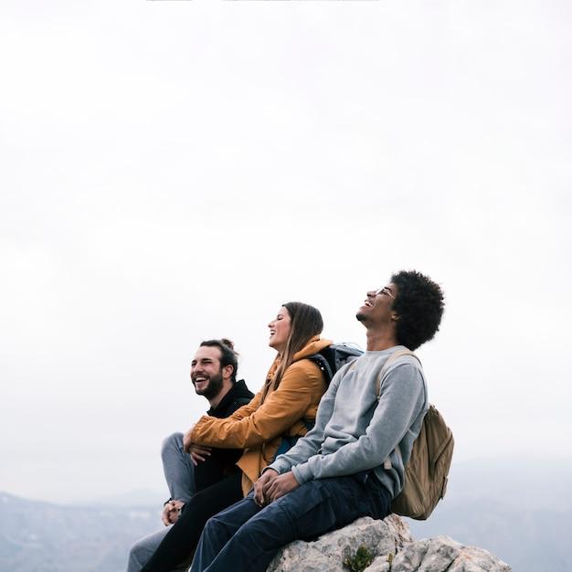 Retrato feliz de un joven amigos sentados en la cima de la montaña Foto gratis